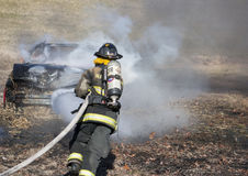 Fireman training on a burning car Stock Photo