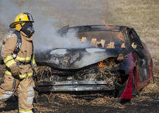 Fireman training on a burning car Stock Images