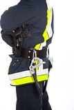 Fireman in uniform with his equipment. Closeup view of the torso of a young fireman in uniform with his equipment attached to his belt and reflective high Royalty Free Stock Image