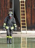 Fireman with the uniform wet after the fire-fighting Services tu Stock Image