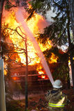 Fireman use water on house in fire Stock Image
