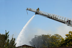Fireman Using Water Cannon From Ladder. This Fireman Is Using A Water Cannon To Fight A Fire Royalty Free Stock Images