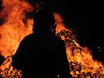 Fireman watches over inferno. Silhouetted fireman watches over pile of wooden pallets burning, taken on the channel island of Alderney, UK Royalty Free Stock Photography