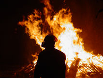 Fireman watching. Fireman in front of a large fire royalty free stock images