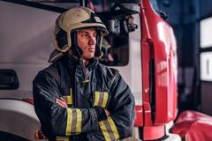 Fireman wearing protective uniform standing next to a fire engine in a garage of a fire department, crossed arms and stock photography