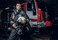 Fireman wearing uniform holding a helmet and looking sideways while standing near a fire truck in a garage of a fire. Fireman wearing uniform holding a helmet stock photography