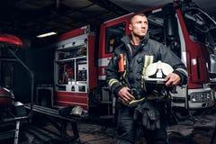 Fireman wearing uniform holding a helmet and looking sideways while standing near a fire truck in a garage of a fire. Fireman wearing uniform holding a helmet stock photo