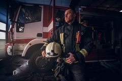 Fireman wearing uniform holding a helmet and looking sideways while standing near a fire truck in a garage of a fire. Handsome fireman wearing uniform holding a stock image