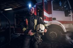Fireman wearing uniform holding a helmet and looking sideways while standing near a fire truck in a garage of a fire. Fireman wearing uniform holding a helmet royalty free stock image