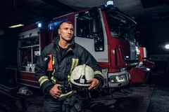Fireman wearing uniform holding a helmet and looking sideways while standing near a fire truck in a garage of a fire. Fireman wearing uniform holding a helmet royalty free stock images