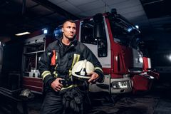Fireman wearing uniform holding a helmet and looking sideways while standing near a fire truck in a garage of a fire. Fireman wearing uniform holding a helmet royalty free stock photos