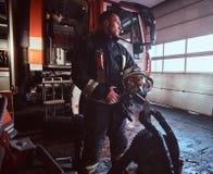Fireman wearing uniform looking outside while standing near a fire truck in a garage of a fire department. Handsome fireman wearing uniform looking outside while stock image