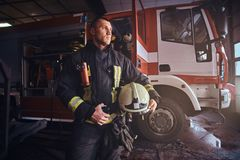 Fireman wearing uniform looking outside while standing near a fire truck in a garage of a fire department. Handsome fireman wearing uniform looking outside while stock photos