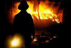 Fireman at Work. A general view of a fieman pictured at work. He is seen here  in silhouette holding a torch as the fire burns out of control in the background Royalty Free Stock Photography