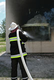 Fireman at work. Firefighter use long water hose for fight a fire Stock Photos