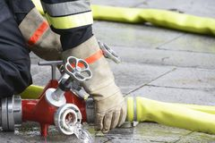 Fireman at work. Hand of a fireman connection a firehose to a connector device Stock Photos