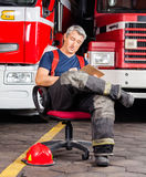 Fireman Writing On Clipboard While Sitting Against Stock Photo
