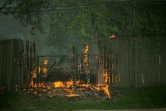 firemans是熄灭一辆分解的灼烧的汽车 库存图片