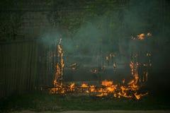 firemans是熄灭一辆分解的灼烧的汽车 库存照片