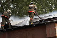 Firemans. The firemans in the form with hose extinguish a fire burning warehouse Royalty Free Stock Photo