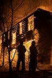 Firemans que intenta a la casa segura en el fuego Bombero Emergency Ext fotografía de archivo