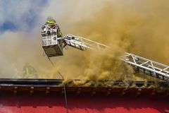 Firemans on a roof fire Royalty Free Stock Images