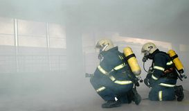 Firemen. Fighting the fire in parking house Royalty Free Stock Images