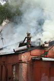 Firemen. Break a roof of a warehouse to liquidate all sites of fire Stock Photo