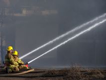 Firemen. Two firemen fighting a fire Stock Photo