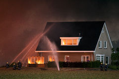 Firemen in action. Firefighters in action to protect a house Stock Image