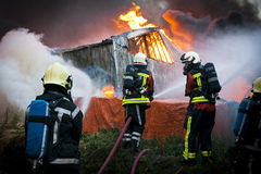 Firemen in action. Group of firefighters in front of a huge fire Stock Photo