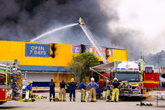 Firemen in action fighting fire at stores. Big clouds of smoke and heat are part of the action for a fire fighter Stock Photography