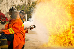 Firemen in action fighting fire during training Royalty Free Stock Photo
