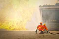 Firemen in action fighting fire during training Royalty Free Stock Photography