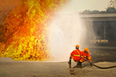 Firemen in action fighting fire during training Stock Photos