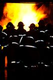 Firemen attacking a fire. Firemen with reflective gear attacking a fire Royalty Free Stock Images
