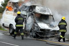 Firemen and Burning Motor Car stock images