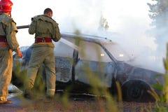 Firemen At Car Crash. Firemen hosing down a burning car at the site of a crash Royalty Free Stock Images