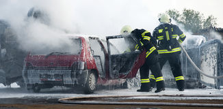 Firemen at car fire Royalty Free Stock Photo