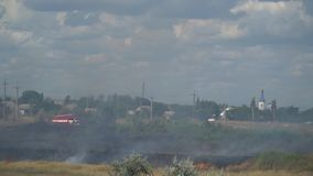 A fire truck goes to a burning field. Firemen on the car go to the field to extinguish a summer fire stock video footage