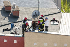 Firemen checking chimney installation on the roof Stock Photo