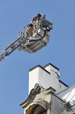 Firemen on a crane fixing a structural building fissure Royalty Free Stock Photo
