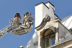 Firemen on a crane fixing a structural building fissure Royalty Free Stock Photography