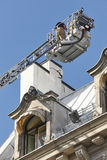 Firemen on a crane fixing a structural building fissure Stock Photo