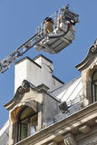 Firemen on a crane fixing a structural building fissure. Royalty Free Stock Photo
