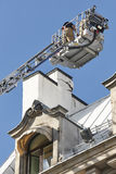Firemen on a crane fixing a structural building fissure. Working Stock Photo