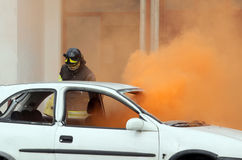 Firemen during exercise to extinguish a fire in a car Stock Photography