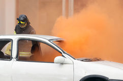 Firemen during exercise to extinguish a fire in a car Royalty Free Stock Photography