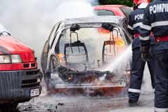 Firemen extinguishes the car on fire. Bucharest, Romania - May 07, 2018: Cars on fire blow up on the streets of Bucharest Stock Image