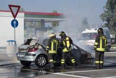 Firemen extinguishing a car fire Stock Image